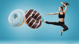 Fit young woman fighting off bad food on a blue background. Concept of diet and healthy lifestile