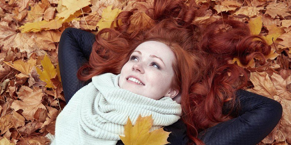redhead girl lying on leaves in city park, fall season