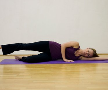 Schritt 1 der Pilatesübung Side Kicks, bei der die Pilateslehrerin auf dem Rücken liegt