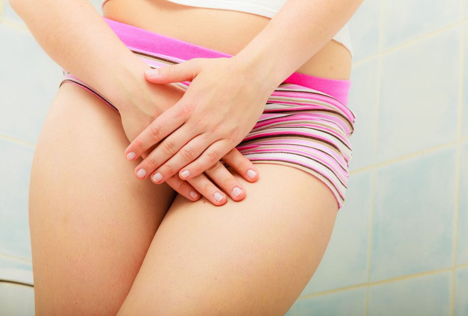 Medical or gynecological problems. Close up woman in panties with hands holding her crotch