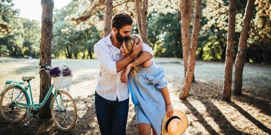Paare spaziert im Wald, Mann umarmt Frau und küsst sie auf den Kopf