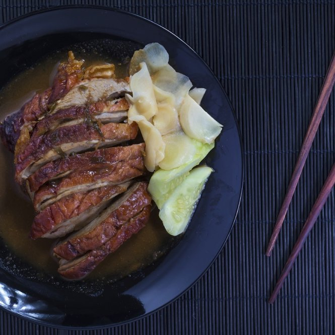 Roast duck and sauces in black dish with chopsticks over Black Sushi mat
