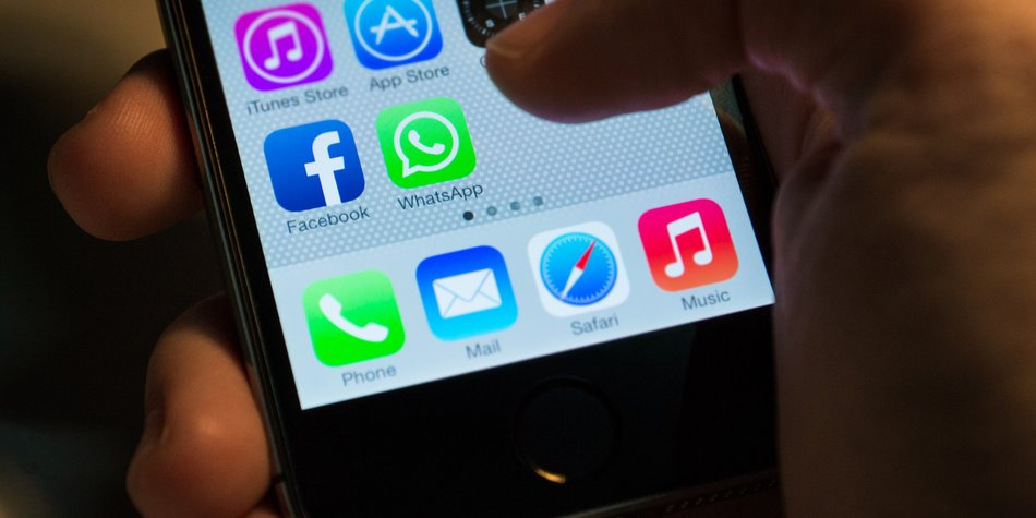 Bangkok, Thailand - February 20, 2014 : Apple Iphone5s held in one hand showing its screen with Facebook and WhatsApp application icons.