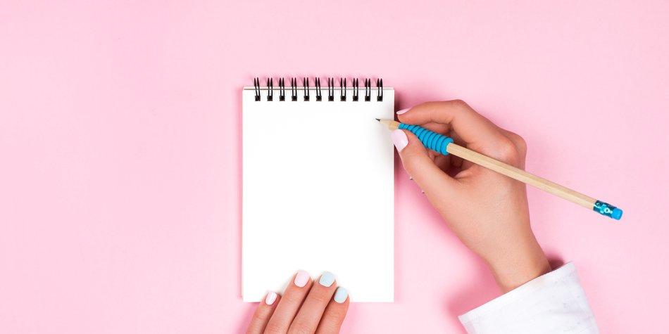 Frauenhand mit Stift und Block
