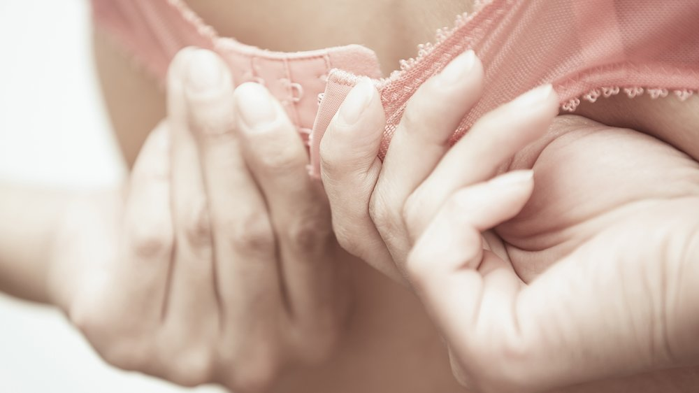 Hands of woman dressing pink brassiere