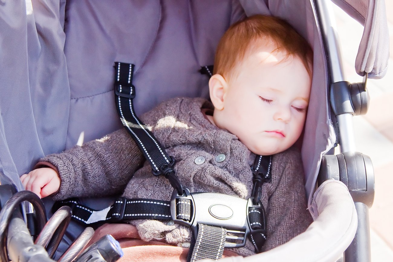 Kind schläft im Kinderwagen