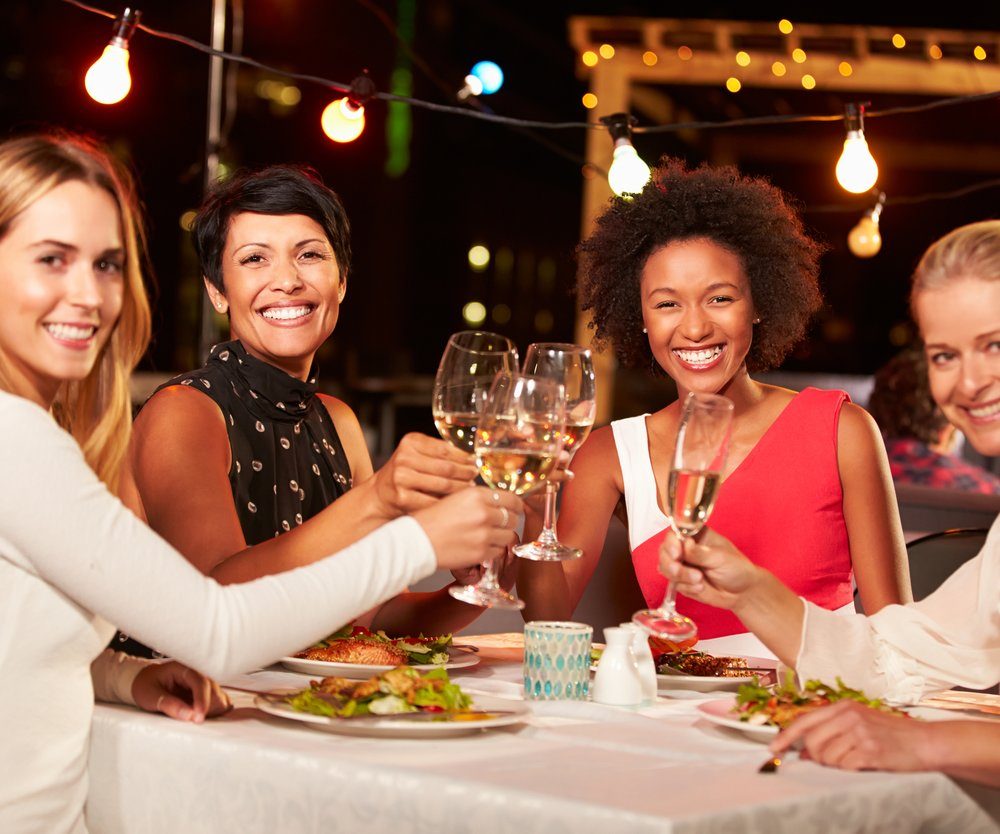 Group of female friends eating dinner at rooftop restaurant, holding glasses of wine, smiling to camera