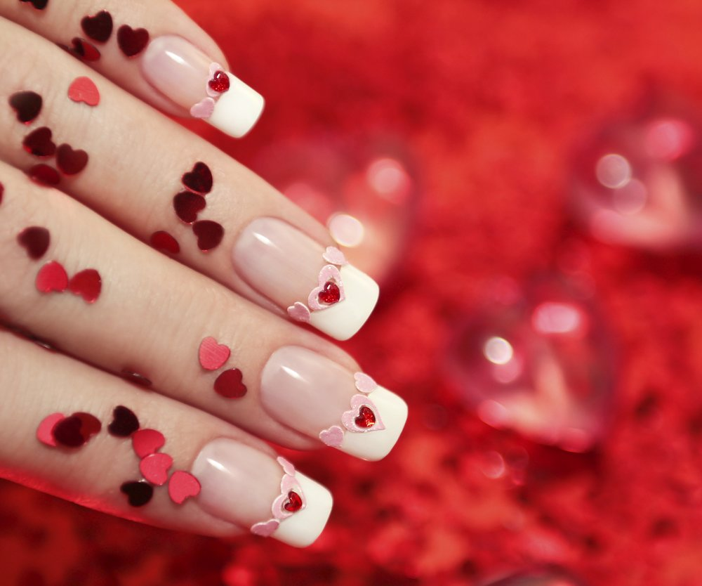 Close-up of French manicured nails and tiny ready hearts