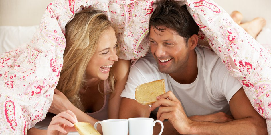 Couple Snuggled Under Duvet Eating Breakfast Smiling