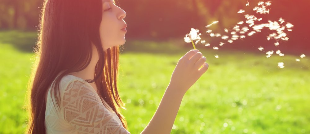 young woman blowing on a white dandelion