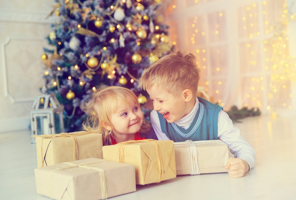 Little boy and girl opening christmas presents in decorated living room