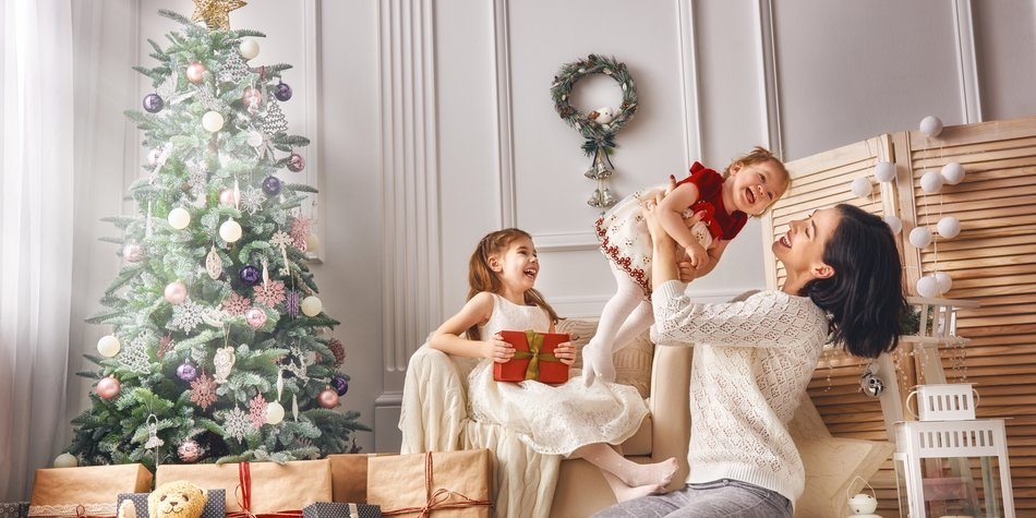Merry Christmas and Happy Holidays! Cheerful mom and her cute daughters girls exchanging gifts. Parent and two little children having fun and playing together near Christmas tree indoors. Loving family with presents in room.