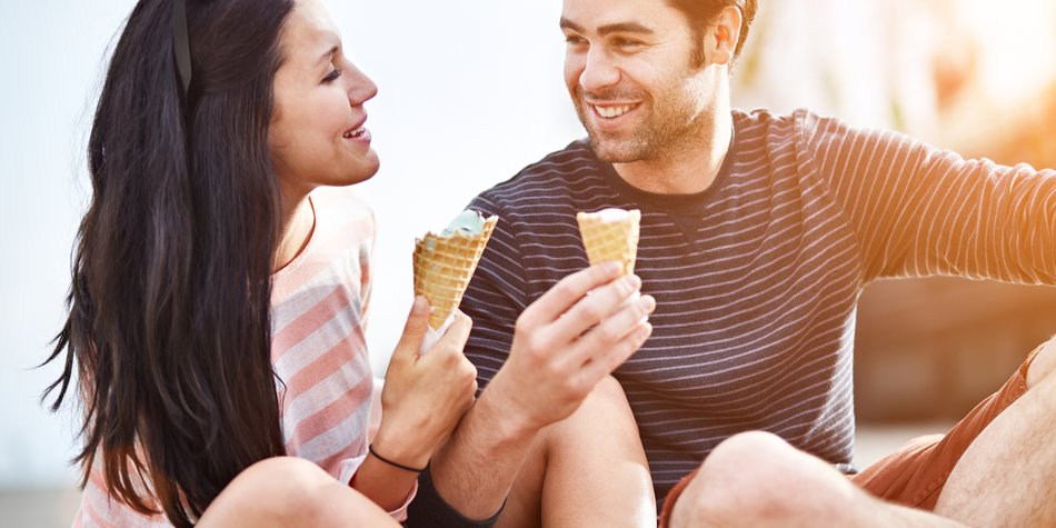 photo of a couple at amusement park sharing ice cream