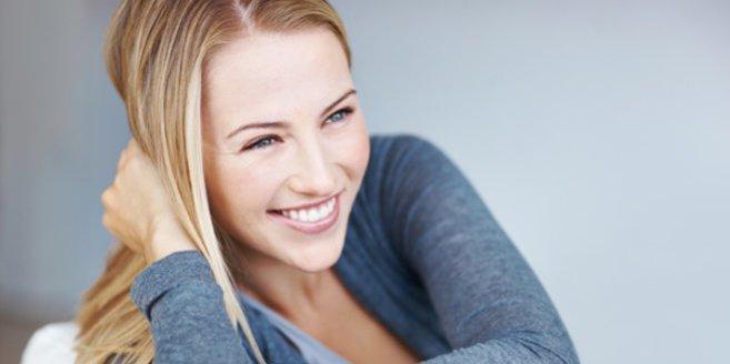 Decapeptyl: Lächelnde Frau liegt auf dem Bauch im Bett