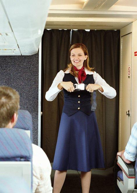 Flugbegleiterin demonstriert Sicherheitinstruktionen