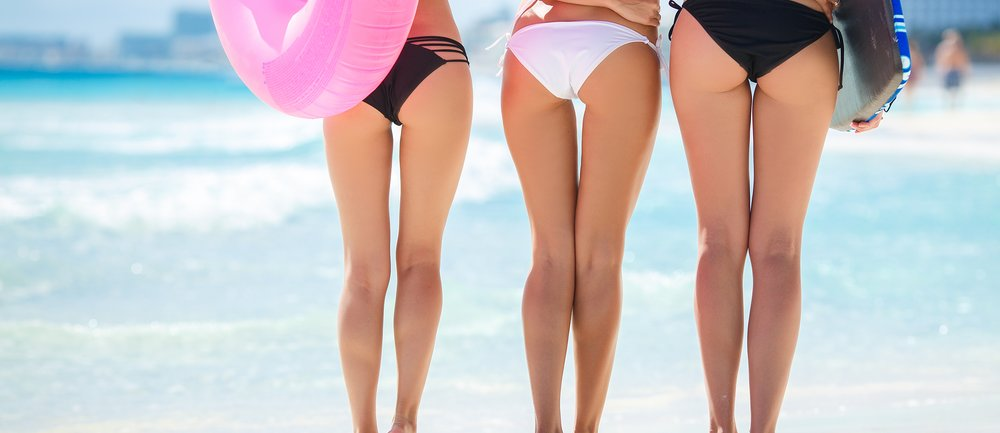 Three young girls with beautiful figure, two girls in black, one girl in a white bikini standing hand in hand on a sandy beach, a girl holding a pink lifeline.