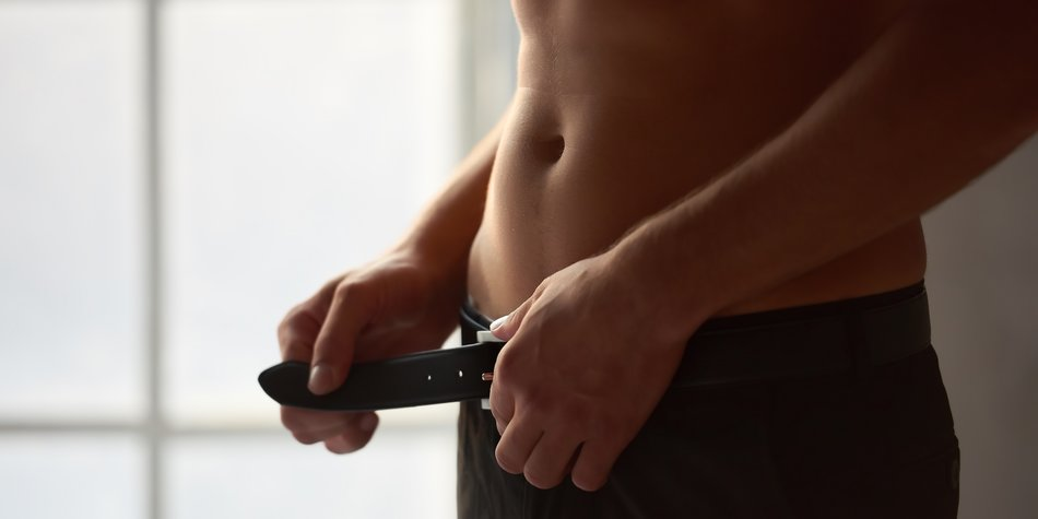 Man unbuckling belt. Attractive male body close up.