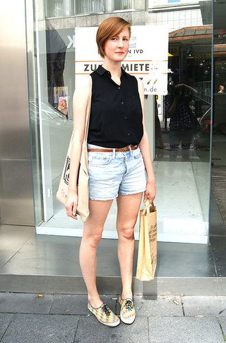 Nora kombiniert eine schwarze Bluse und Jeansshorts simpel, aber gekonnt.