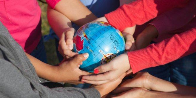 Bilingualer Kindergarten: Kinder halten eine Weltkugel in der Hand