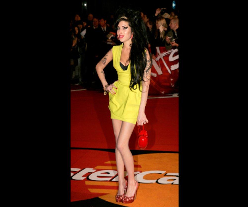 Amy Winehouse in einem gelben Kleid