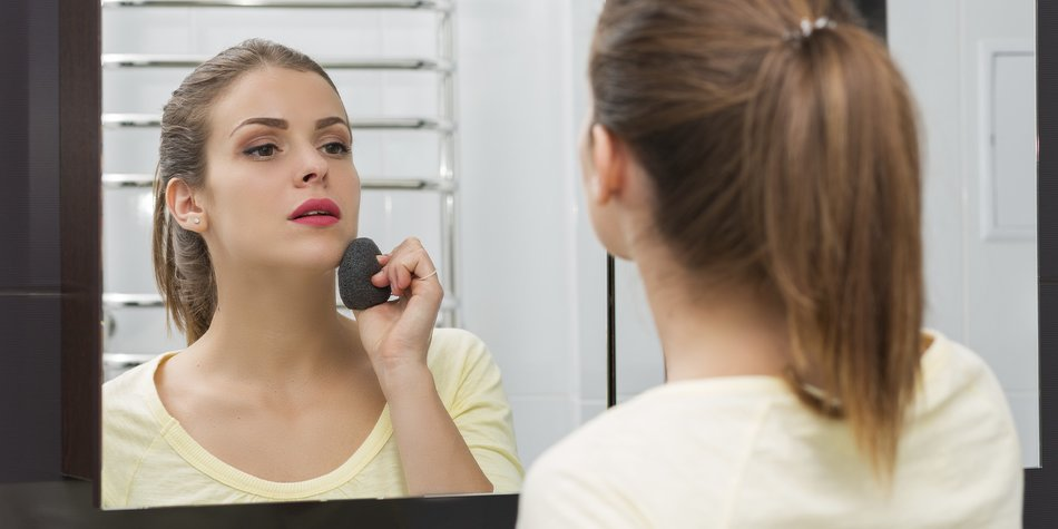 Beautiful girl removing makeup with Konjac sponge