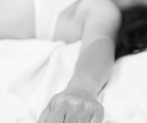 Female hand pulling white sheets in ecstasy, orgasm.