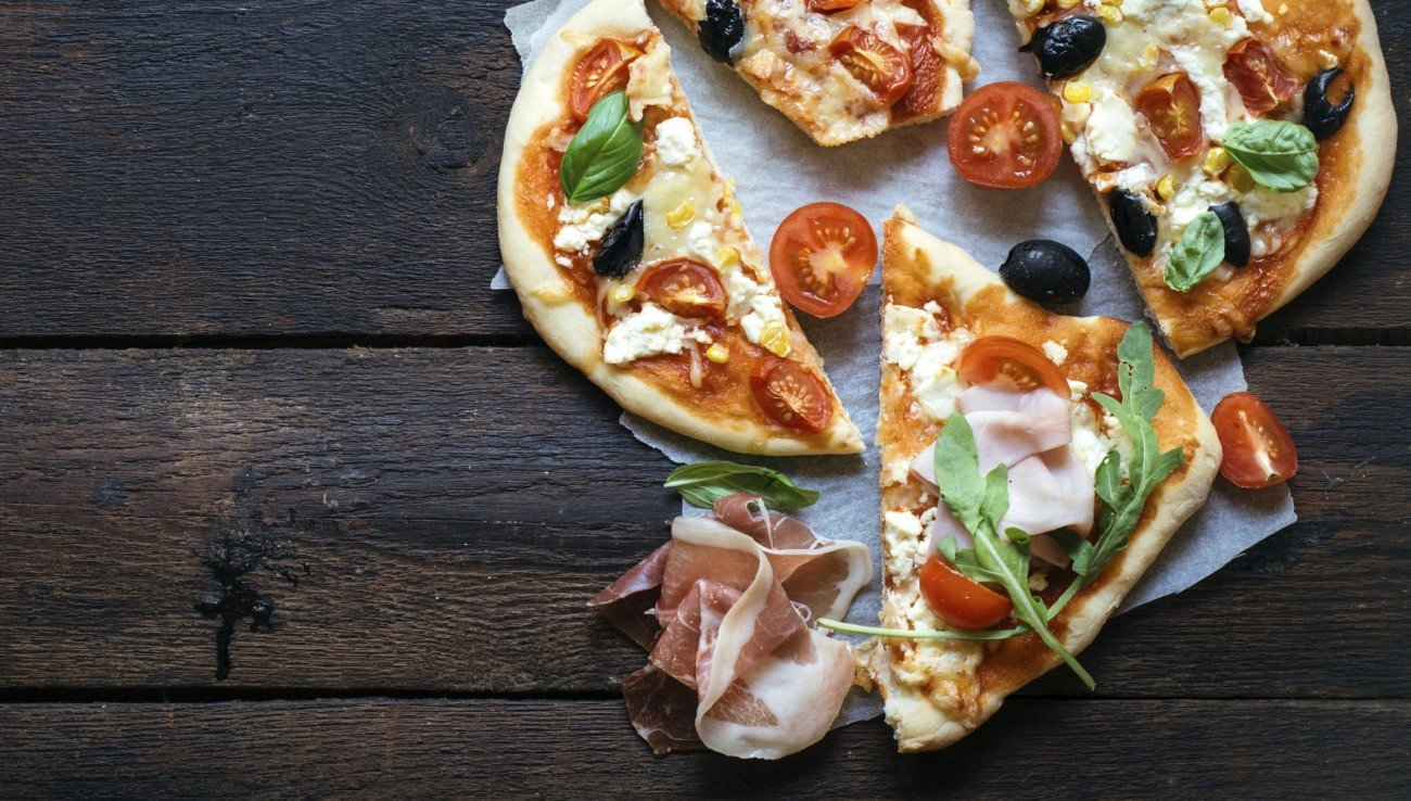 Slices of mini pizza variety served on wooden board and background,from above and blank space