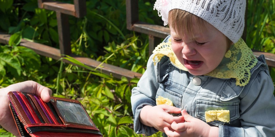 crying baby with empty purse outdoors