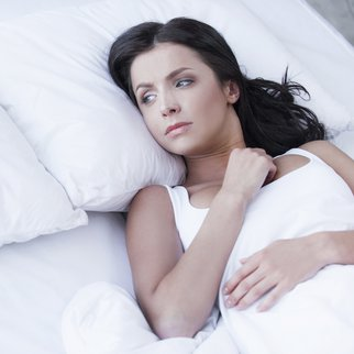 Depressed young women lying on the bed and looking on empty pillow