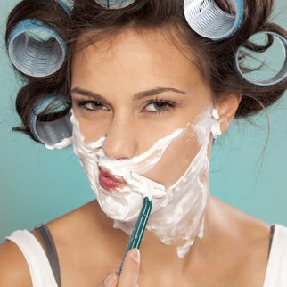 attractive young woman shaving her face