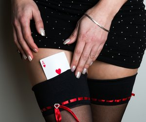 Sexy lady with poker red ace combination over black stocking legs