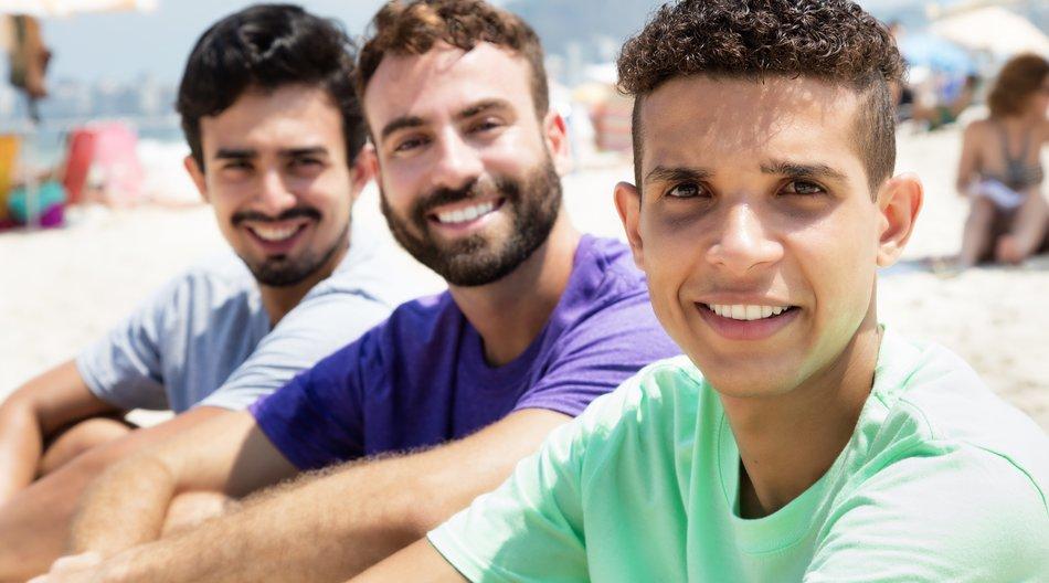 Three friends outdoor at beach looking at camera