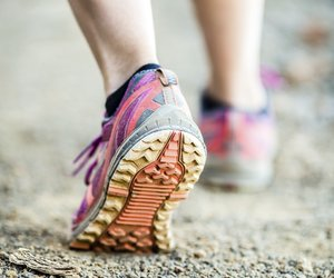 Walking or running legs on trail, adventure and exercising in mountains nature, dirt road