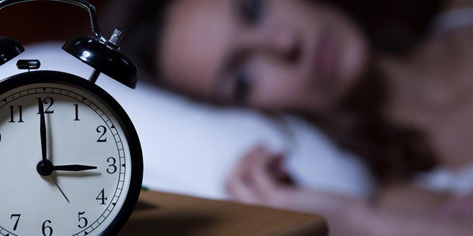 Frau im Bett mit Wecker
