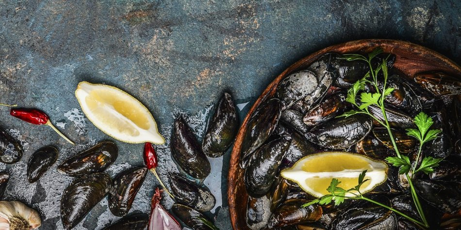 Fresh black mussels in wooden bowl with lemon and ingredients for cooking on dark rustic background, top view, border, vertical. Seafood concept