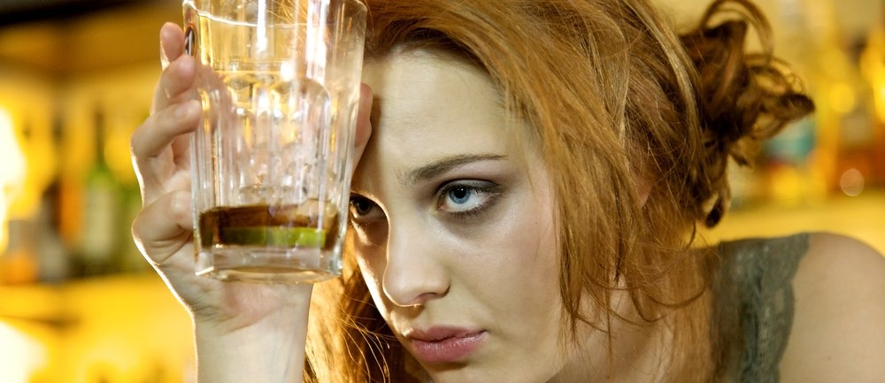 Young woman with a hangover holding her almost empty cocktail glass