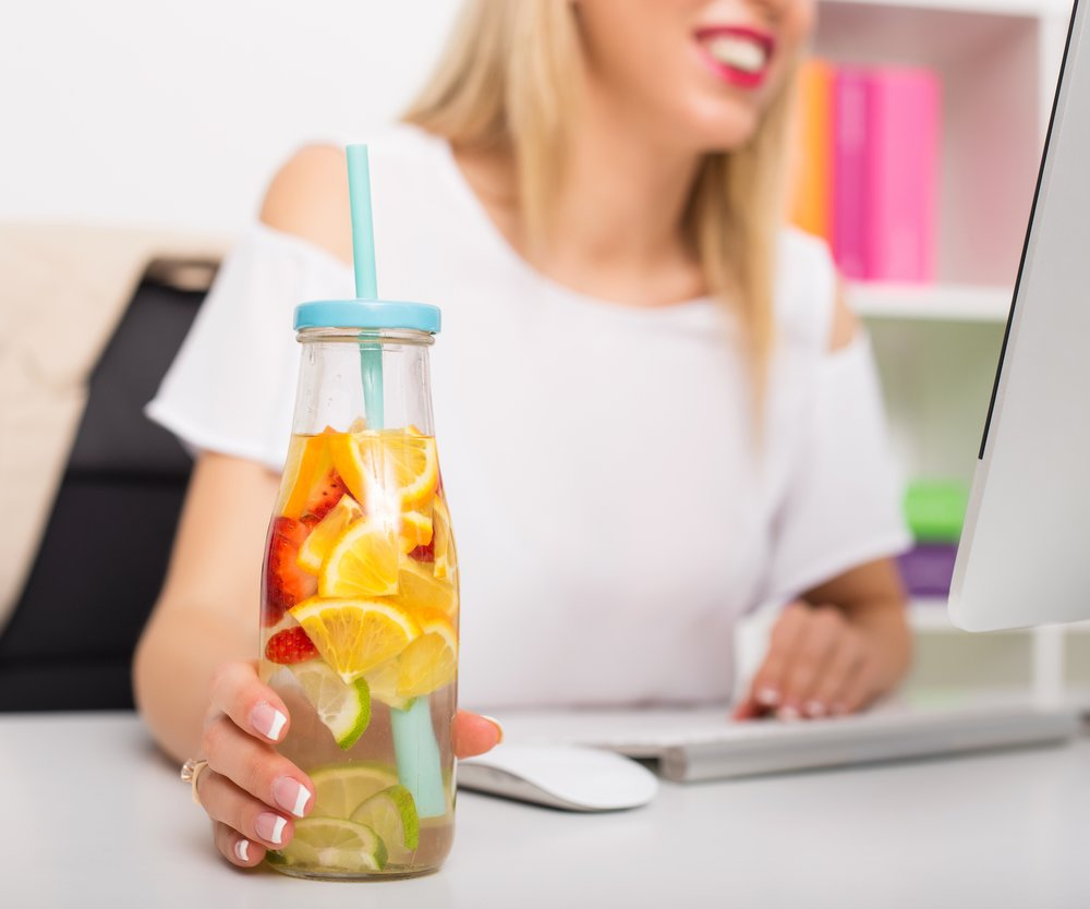 Woman at the office having re-freshening drink