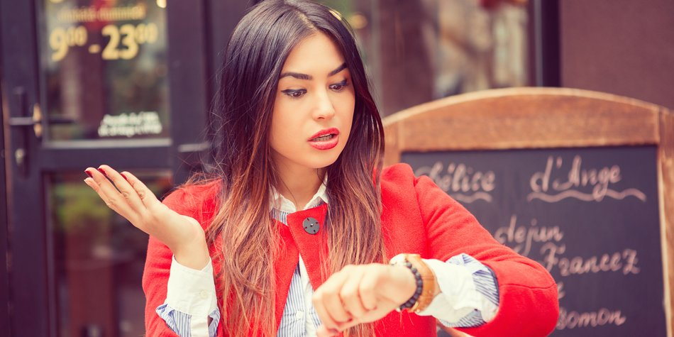 Portrait of shocked young woman holding hand with wrist watch and looking at camera isolated on coffee shop outside terrace background. Busy graphic concept, outdoors coffee shop background