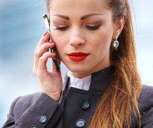 Business-Frau telefoniert und schaut auf ihre Uhr
