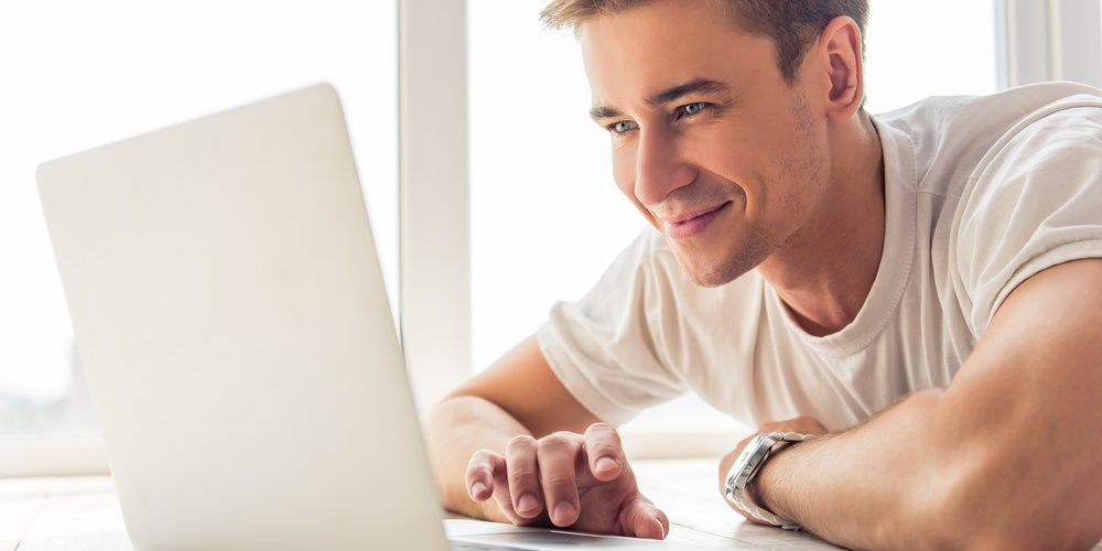 Handsome young businessman in casual clothes is using a laptop and smiling while lying at home on the floor before the windows