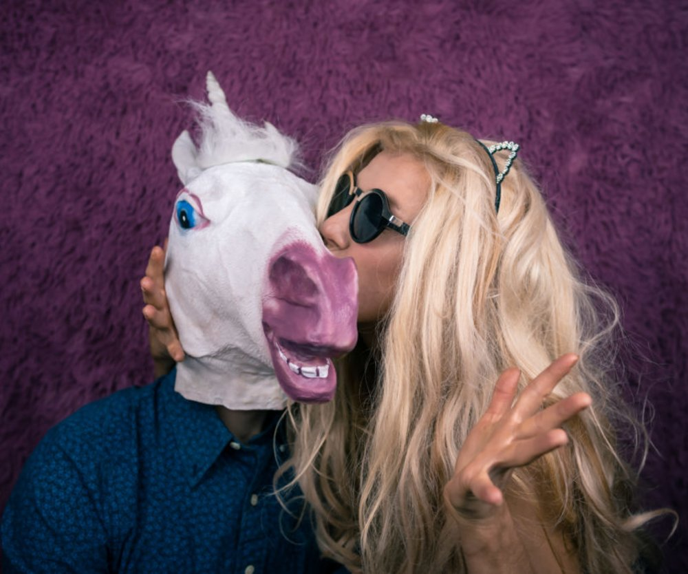 Freaky young woman in sunglasses and kitty ears kissing happy unicorn on the purple background. Expressive blond with strange guy. Unusual people sits together and shows emotions