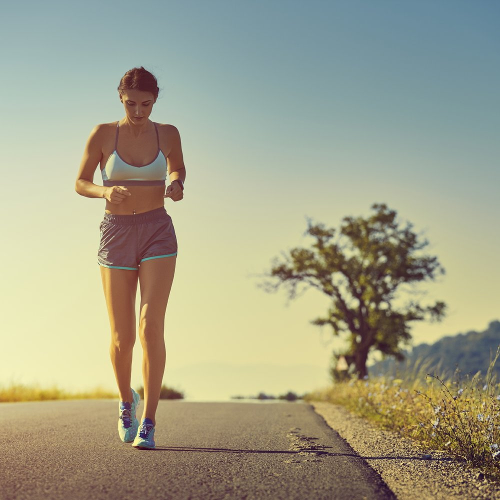 Beautiful fit woman in sport shorts running on a road at sunrise or sunset. Healthy lifestyle concept. Toned with warm instagram like filter.