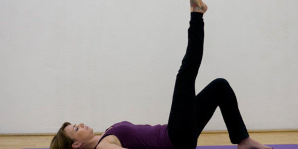 Schritt 1 der Pilatesübung Single Leg Circles, bei der die Pilateslehrerin auf dem Rücken liegt