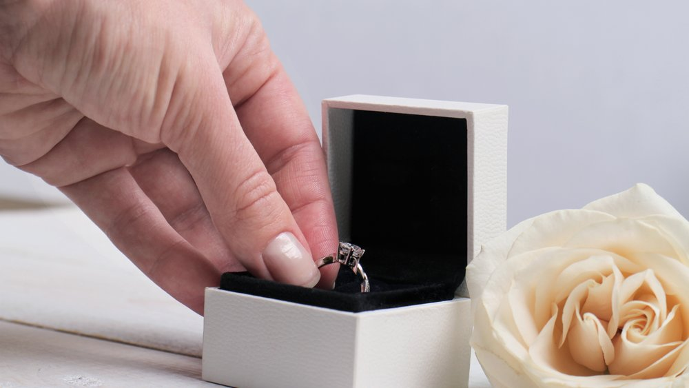 Engagement ring box in bride hands. Closeup of woman hand holding jewellery. Love, Wedding, Proposing, Marriage concept.