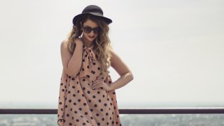 Pin up girl wearing a sexy polka dot dress and a black hat. City Scape panorama