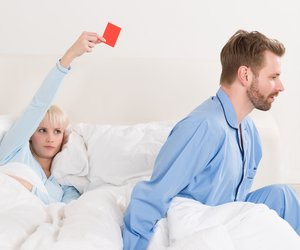 Unhappy Young Woman Showing Red Card To Man In Bed
