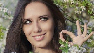 Eine Frau lächelt mit einer Tablette in der Hand