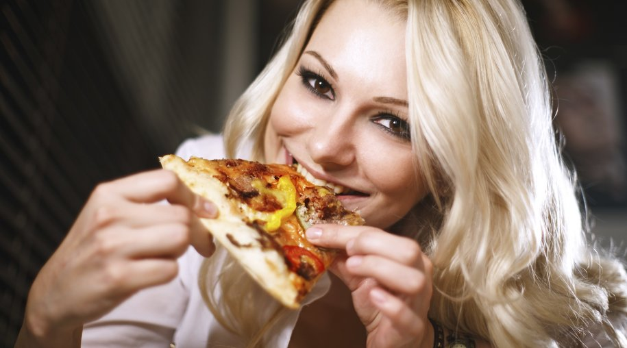 Young woman in a white shirt eats pizza