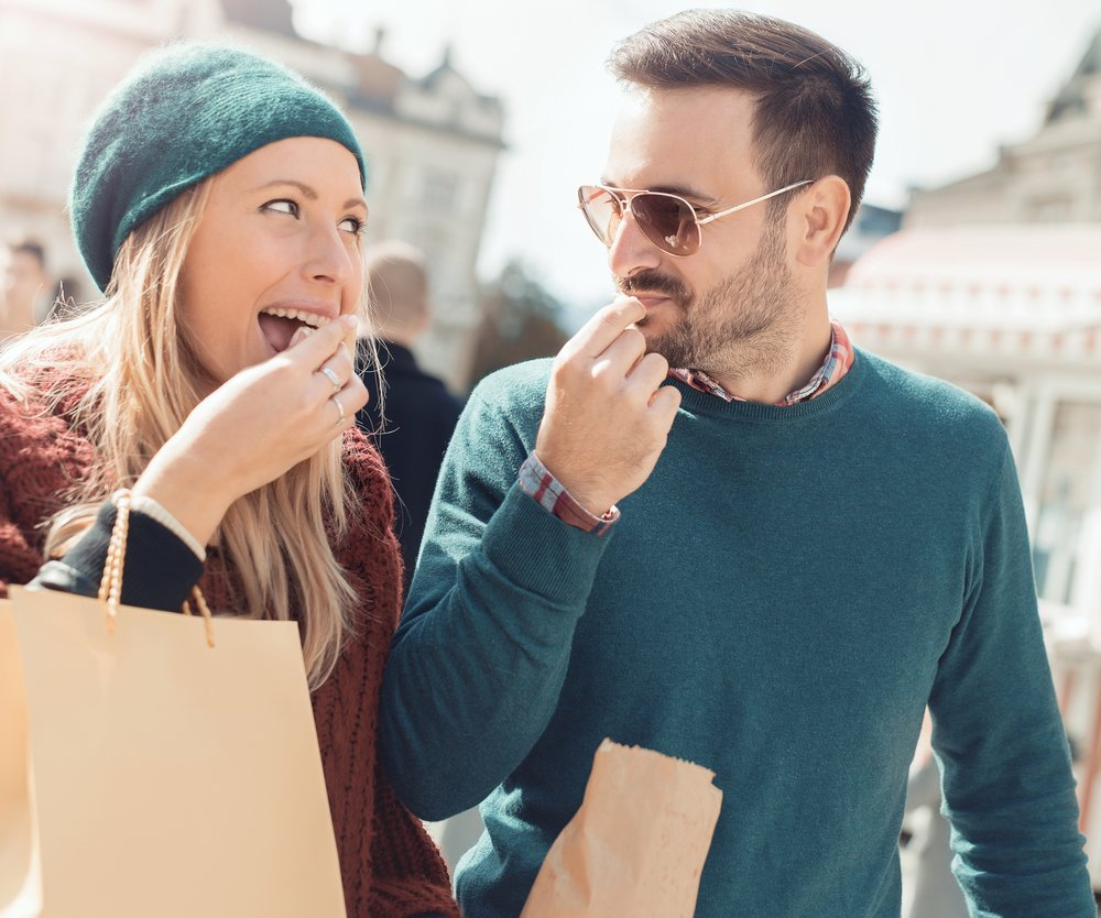 Handsome young couple holding shopping bags and eating popcorn while walking down the street. Consumerism, shopping, lifestyle concept