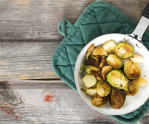 Delicious browned sauteed diced brussels sprouts in a saucepan on an oven cloth, overhead view on an old rustic weathered wooden table top with grungy boards and copyspace